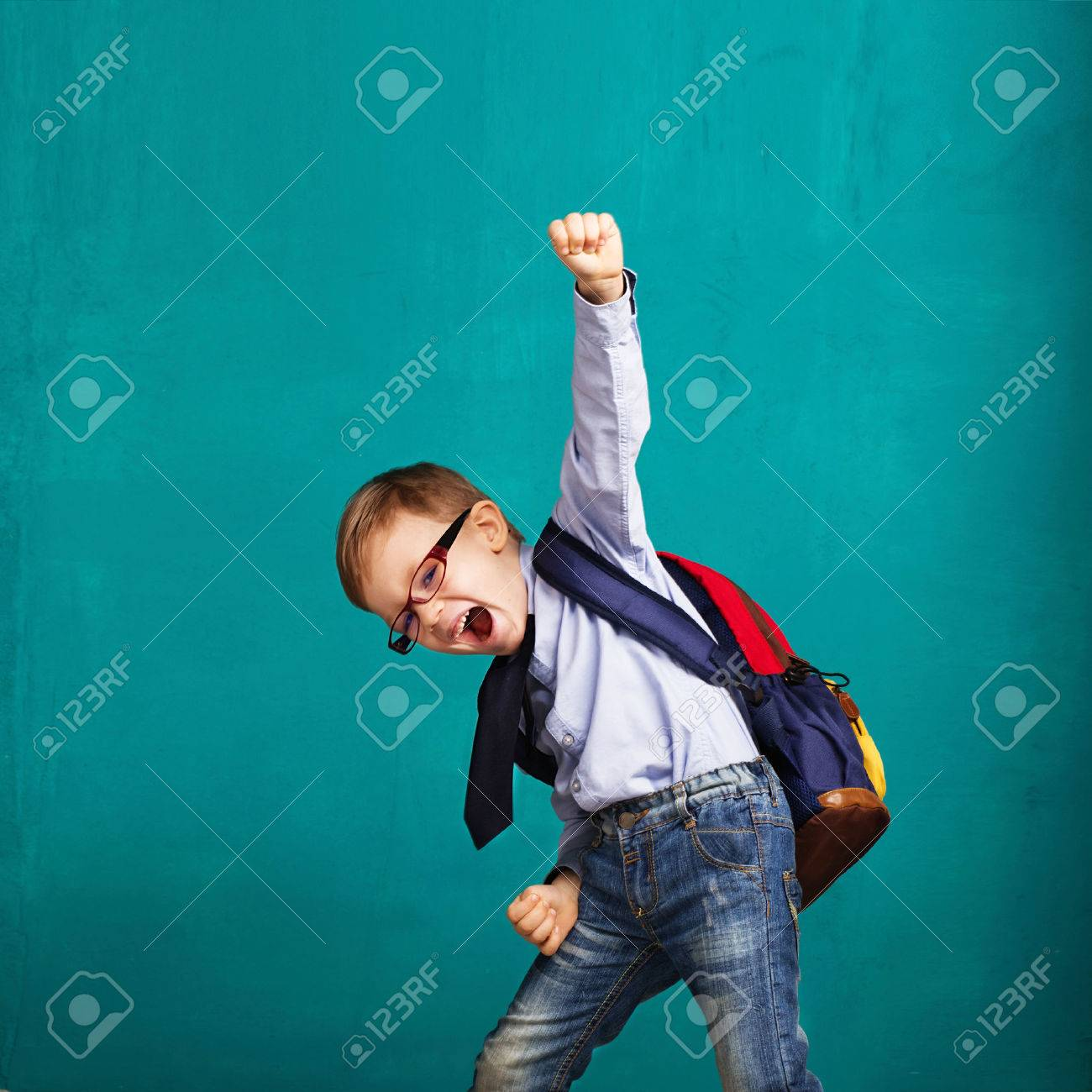 Cheerful smiling little boy with big backpack jumping and having fun against blue wall. Looking at camera. School concept. Back to School - 54370615
