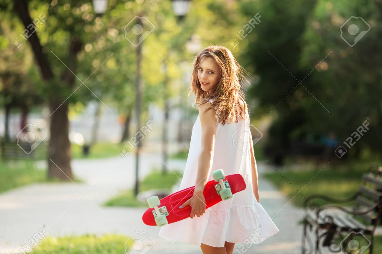 a91da29265b70 Portrait De Jolie Fille Urbaine En Robe Blanche Avec Une Planche à  Roulettes Rose. Portrait D une Femme Souriante Heureuse. Jeune Fille Debout  Avec Une ...