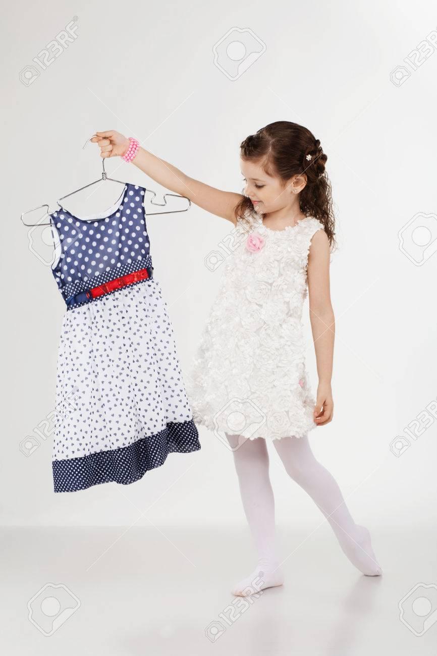 92cd7e7f73dd Banque d images - Petite femme d essayer de nouveaux vêtements sur fond  blanc. Petite fille choisit robe. Petite fille et vêtements shopping cintres