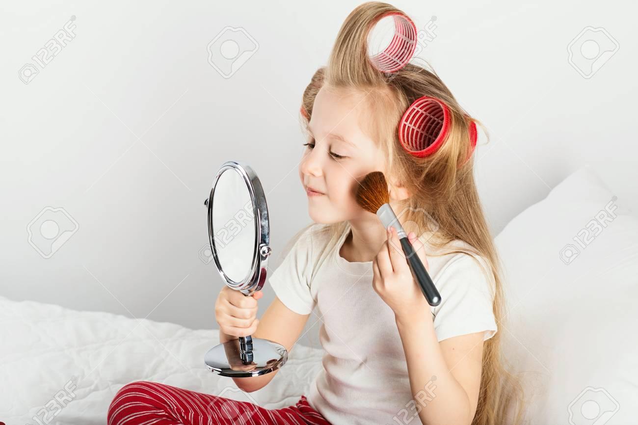 8dfbf6d336ad1 Banque d images - Mode petite fille maquillée de miroir. Adorable bébé joue  avec maquillage de maman. Portrait d une petite fille drôle avec un curleur  ...