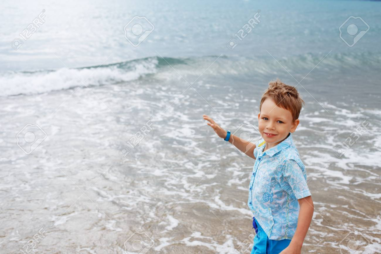 328306978 little boy in shirt and shorts on the beach sand. Little boy having fun on