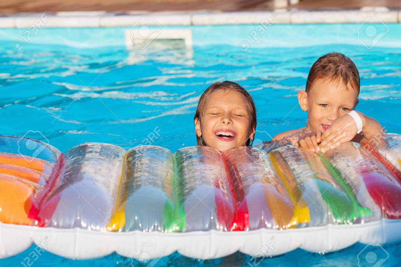 Little children playing and having fun in swimming pool with..