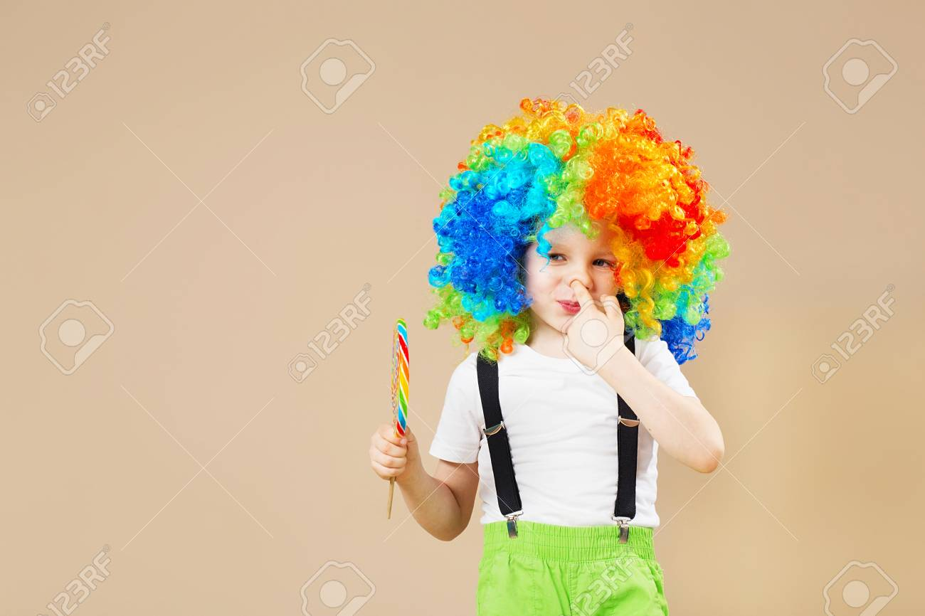 Happy clown boy in large colorful wig. Let's party! Funny kid clown. 1 April Fool's day concept. child eating lollipop. Finger in the nose. Picking in the nose. - 92097217