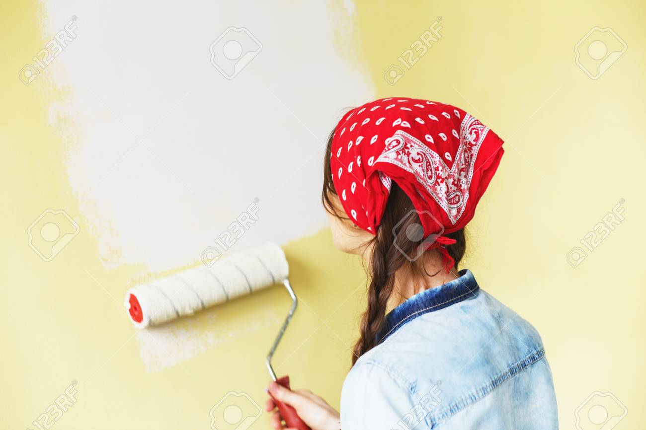 Beautiful Girl In Red Headband Painting The Wall With Paint Roller ...