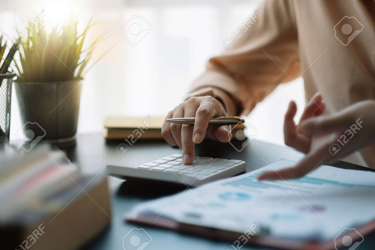 businessman working on desk office with using a calculator to calculate the numbers, finance accounting concept. - 167897122
