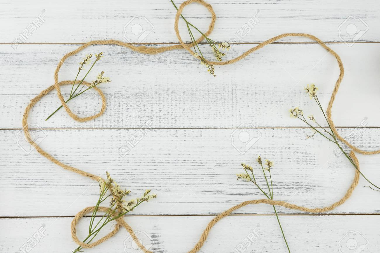 Cuerda Marrón Decorar Con Flores De Caspia Amarillo Limonium Sobre Fondo Blanco De Madera Con Espacio De Copia En El Centro