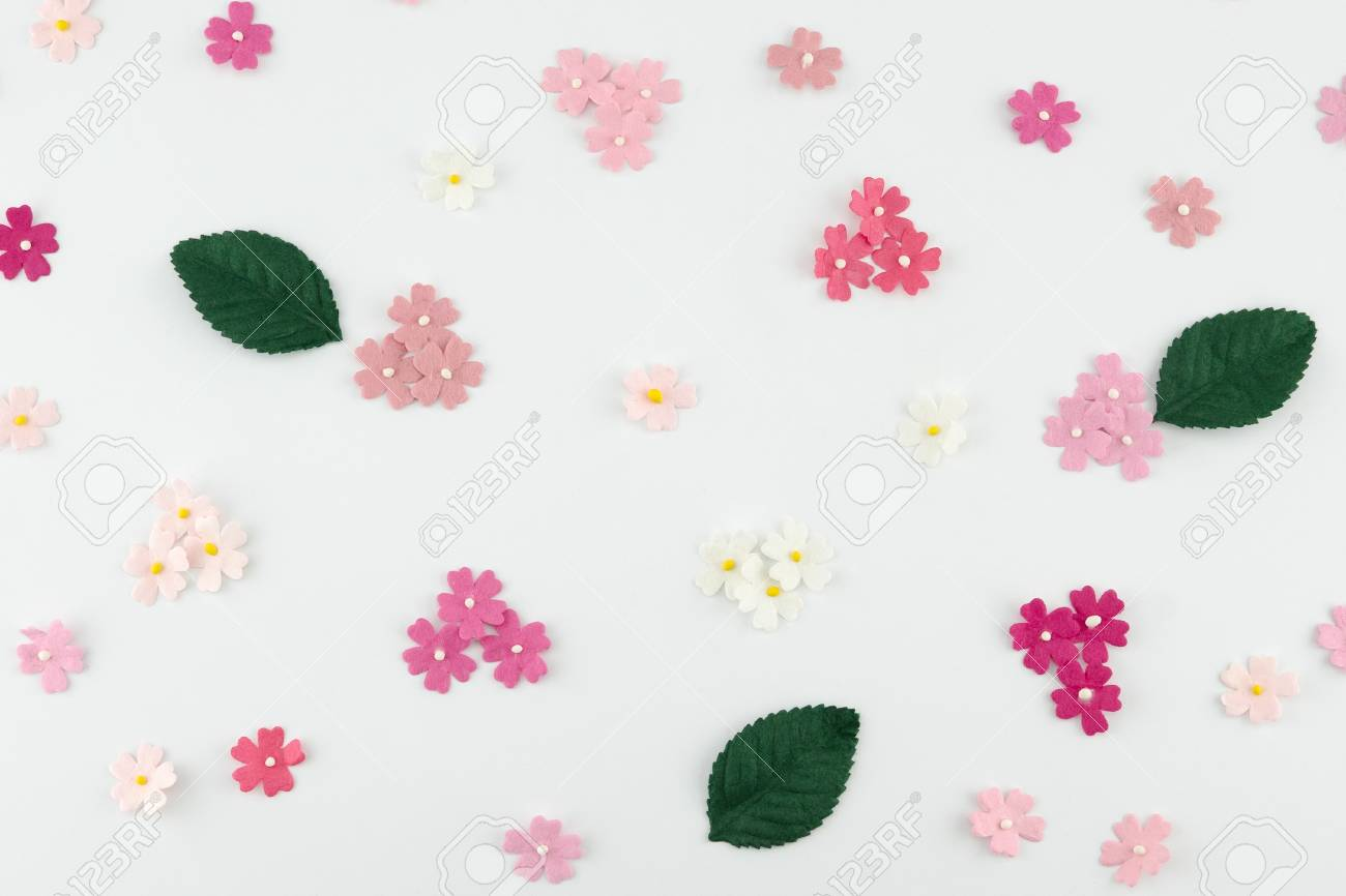 Pink Paper Flowers And Green Leaves On White Background Stock Photo