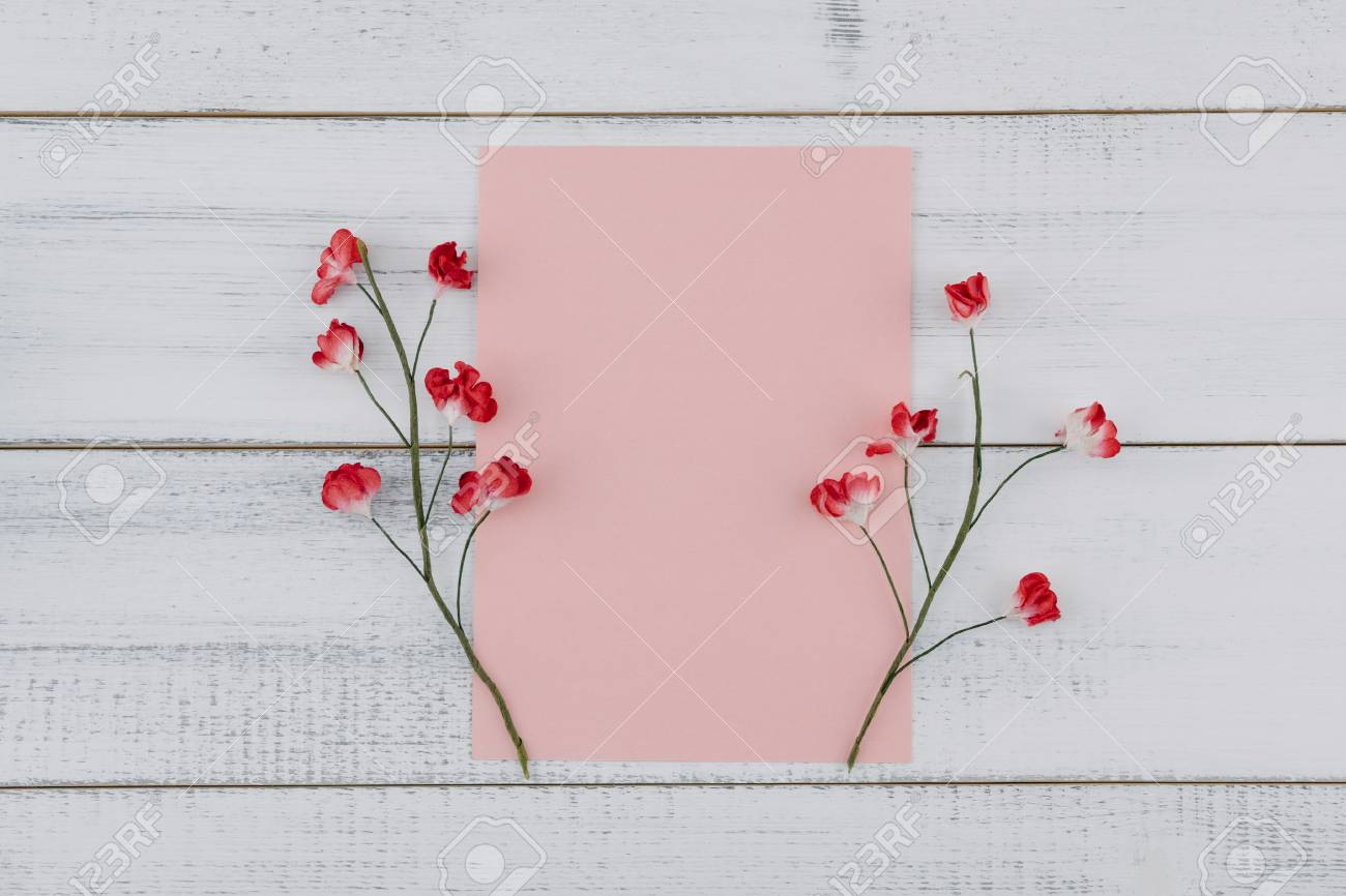 bab14a50ae5 Blank pink card decorate with red paper flowers on white wood background  Stock Photo - 100141369
