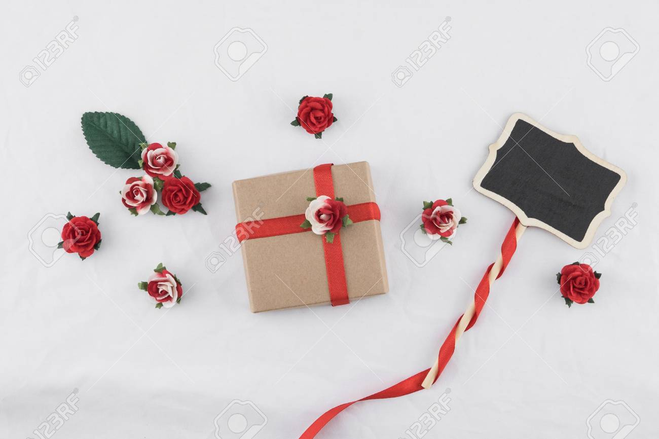 Brown gift box and tiny blackboard decorate with red rose paper brown gift box and tiny blackboard decorate with red rose paper flowers and ribbon on white mightylinksfo