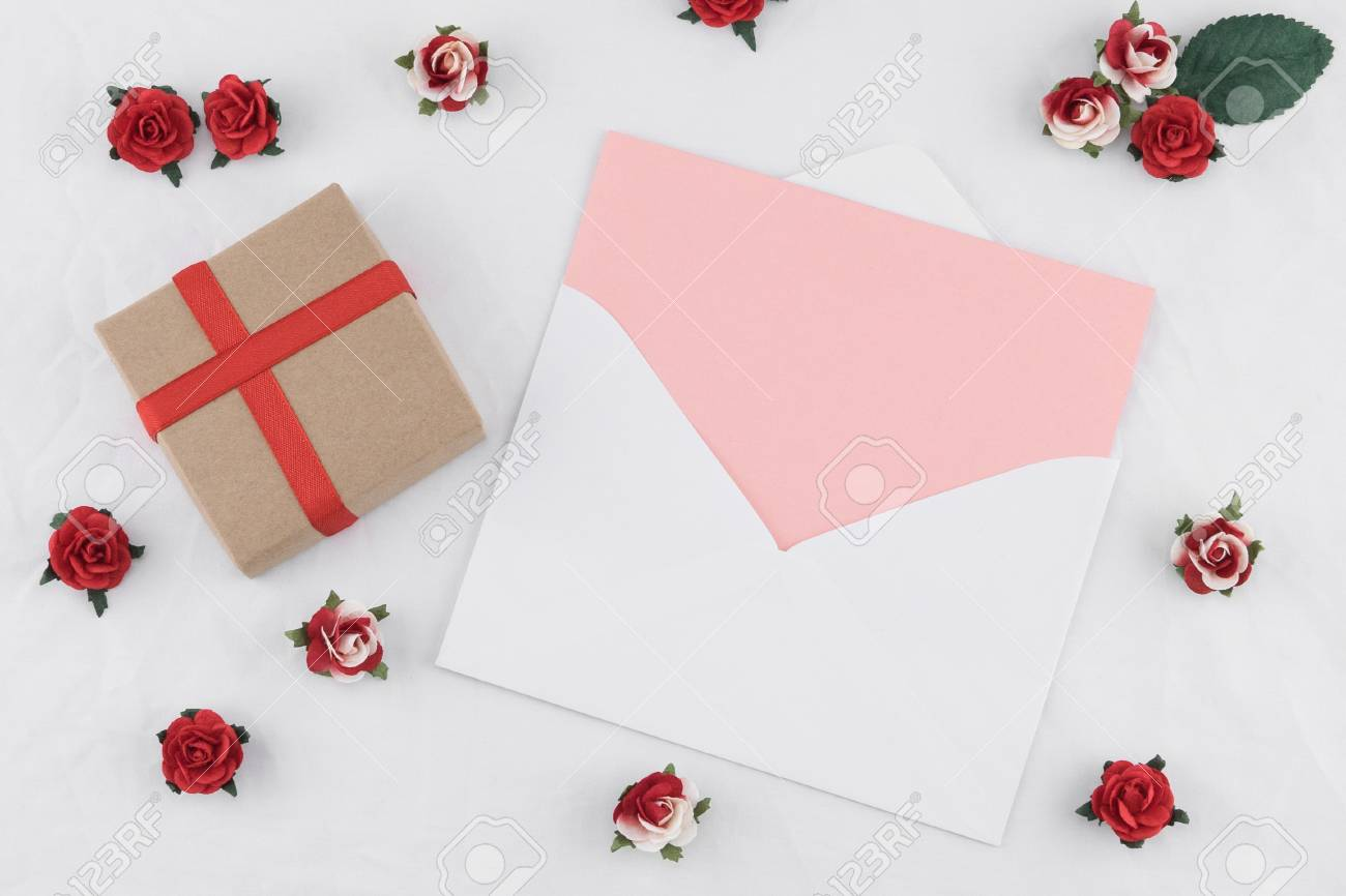 Brown Gift Box And Pink Card In White Envelop Decorate With Red Rose