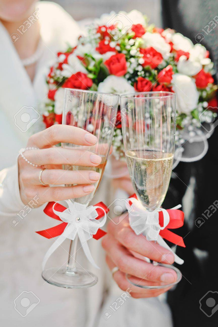Bride And Groom Holding Beautifully Decorated Wedding Glasses