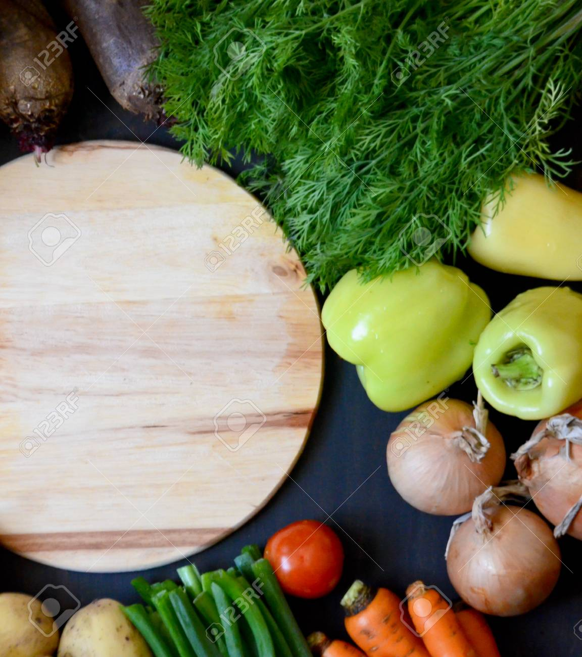 Wooden Round Cutting Board Next To The Vegetables On Black Background Stock Photo Picture And Royalty Free Image Image 86497769
