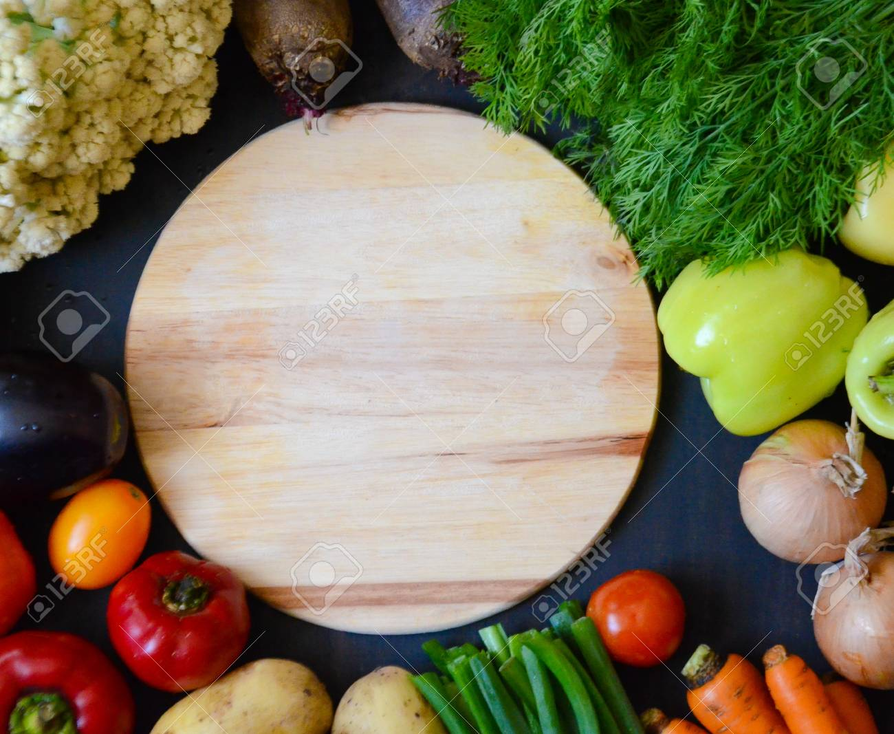 Wooden Round Cutting Board Next To The Vegetables On Black Background Stock Photo Picture And Royalty Free Image Image 86677862