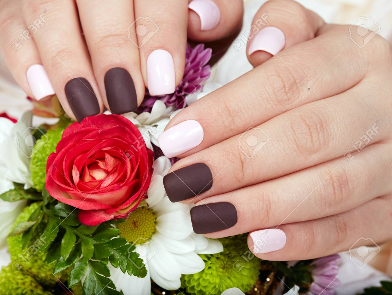 Hands With Pink And Purple Manicured Nails And A Bouquet Of Flowers ...