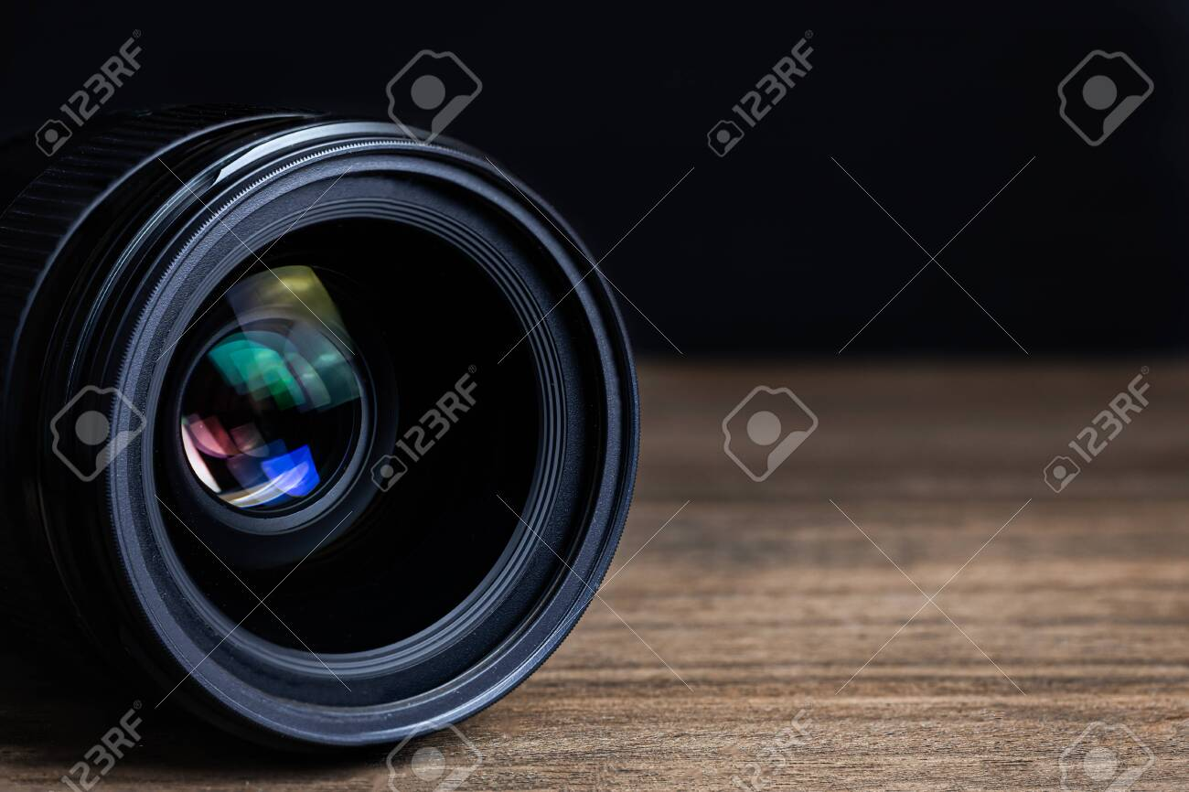 Closeup camera lens on a wooden floor with black dark background blur detail object isolated - 147916110