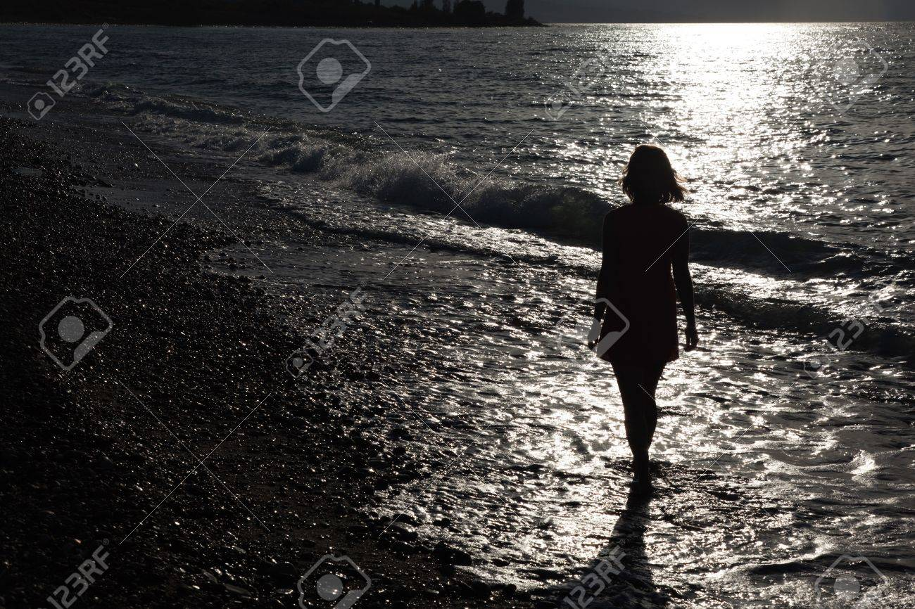 Girl walking on the beach at sunset Stock Photo - 7823435