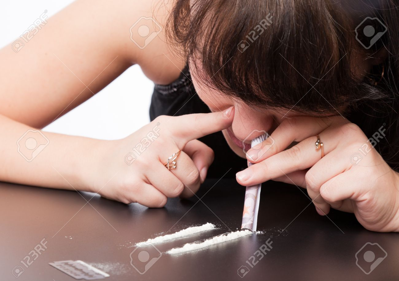 a girl is sniffing cocaine (imitation). isolated on a white background Stock Photo - 8568483