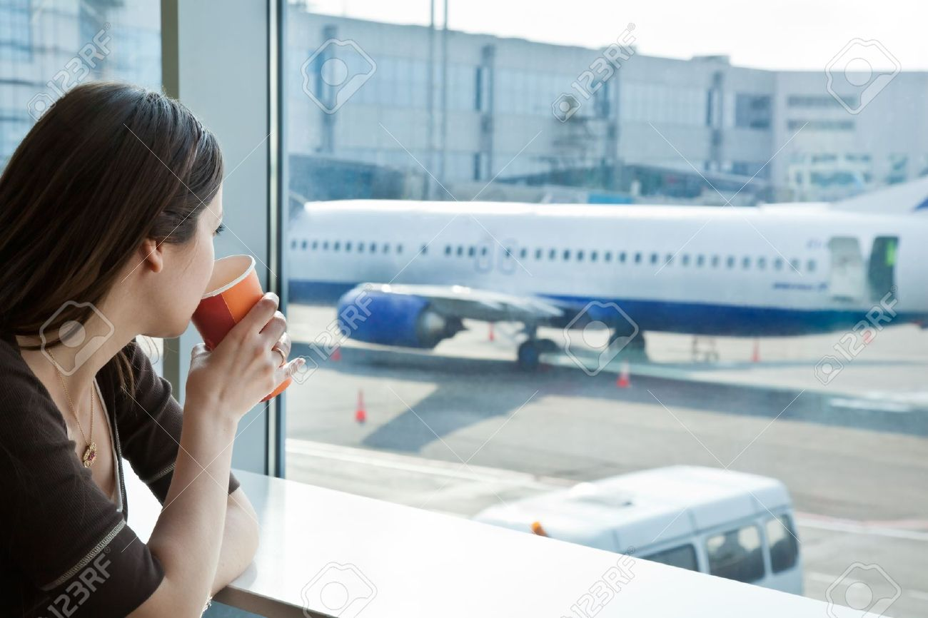 Young woman is drinking coffee in airport - 10874010