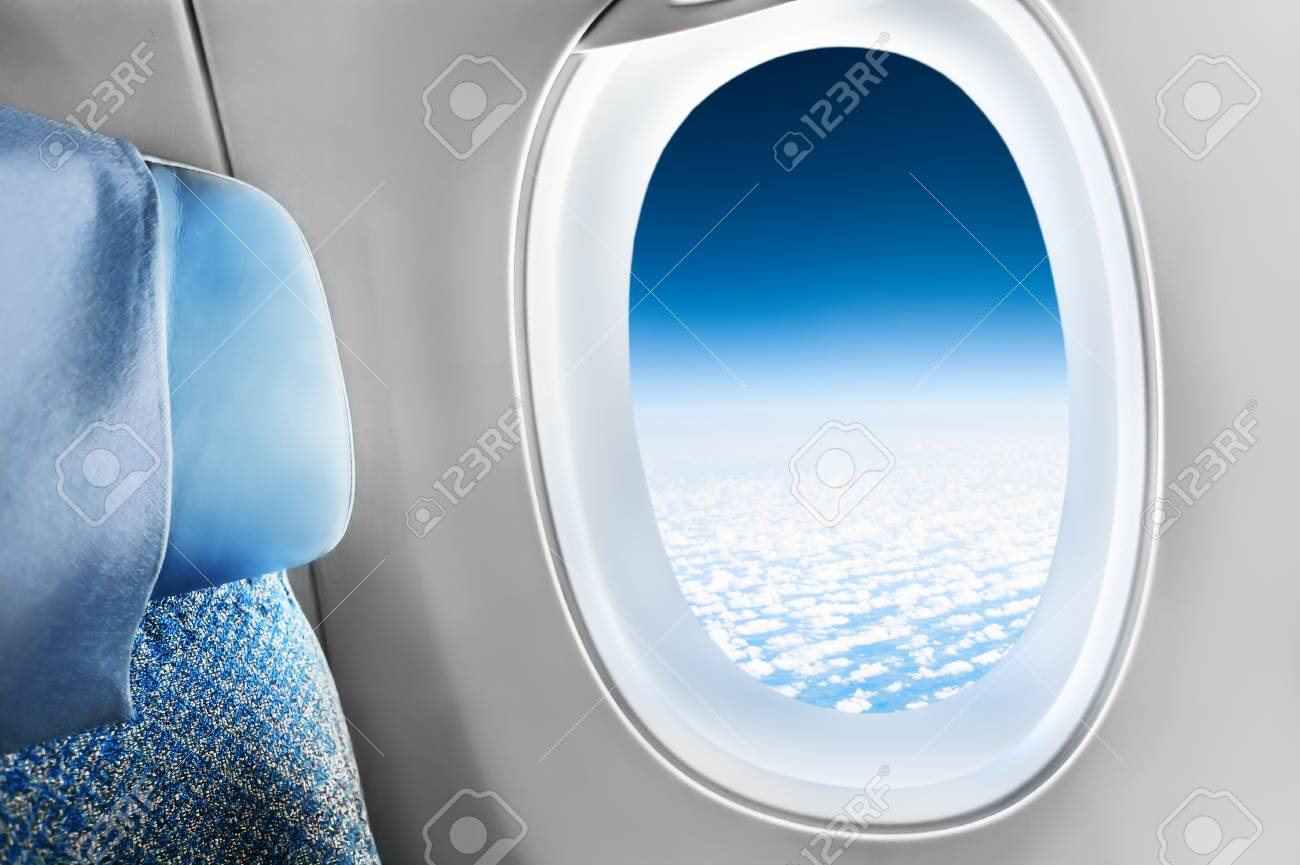 Passenger Seat In Airplane And Window View Of Sky With Clouds