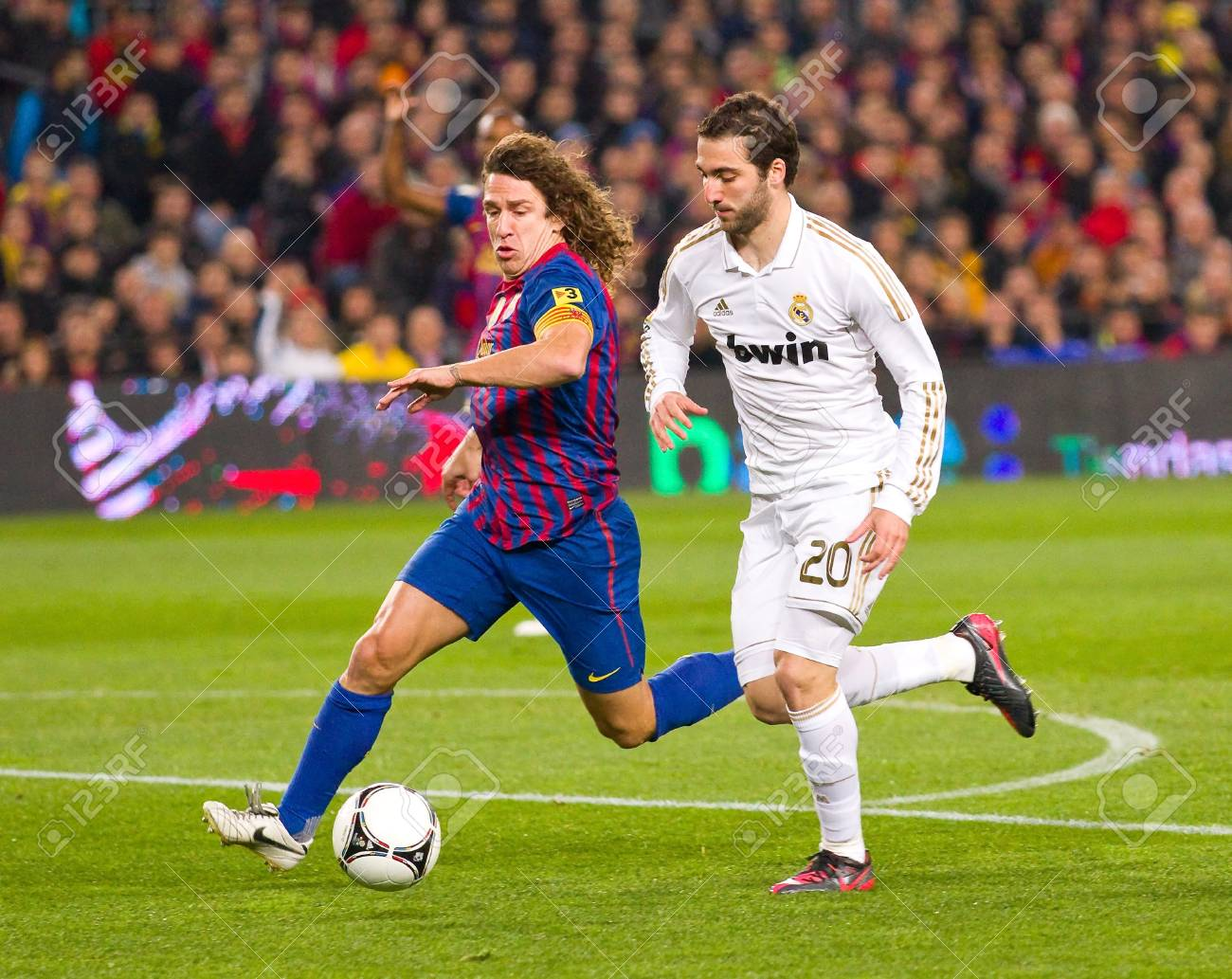 BARCELONA - JANUARY 25: Carles Puyol and Gonzalo Higuain in action during the Spanish Cup match between FC Barcelona and Real Madrid, final score 2 - 2, on January 25, 2012, in Barcelona, Spain Stock Photo - 14755534