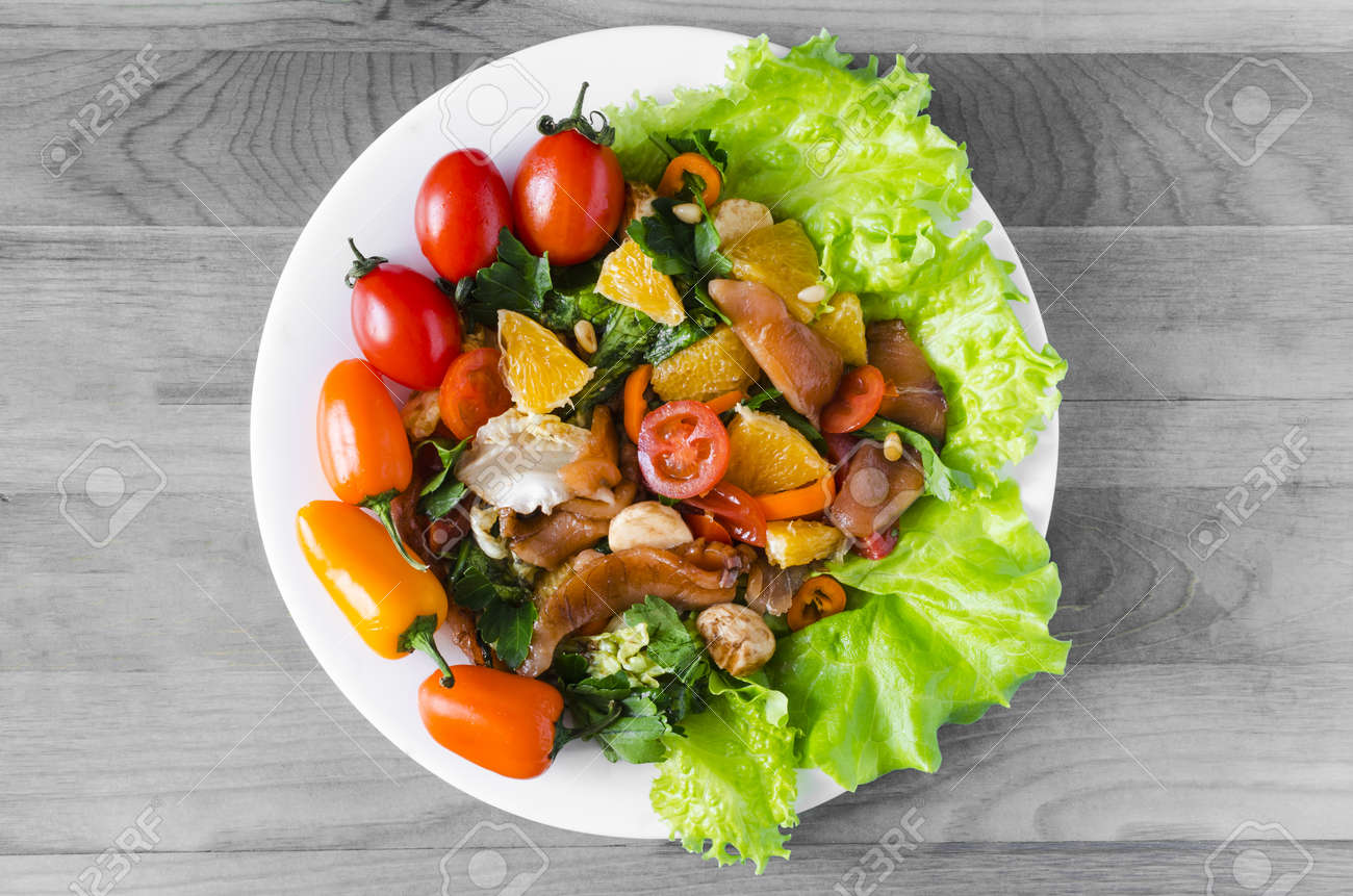 appetizer with fish and vegetables on a white plate decorated with tomatoes, herbs and sweet peppers black and white background - 156880830