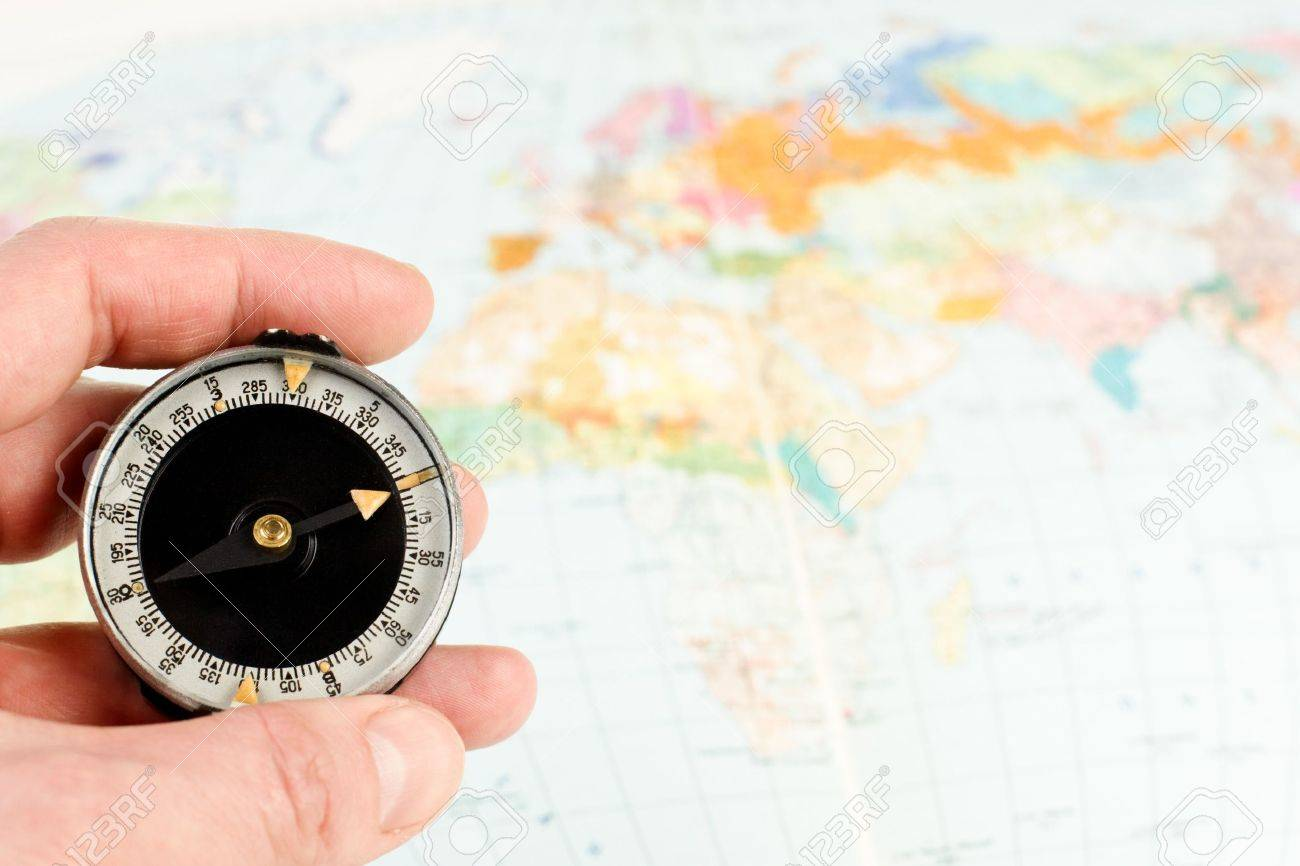 Map Of The World With Compass.Hand Holding Compass With Map Of The World In Background Stock Photo