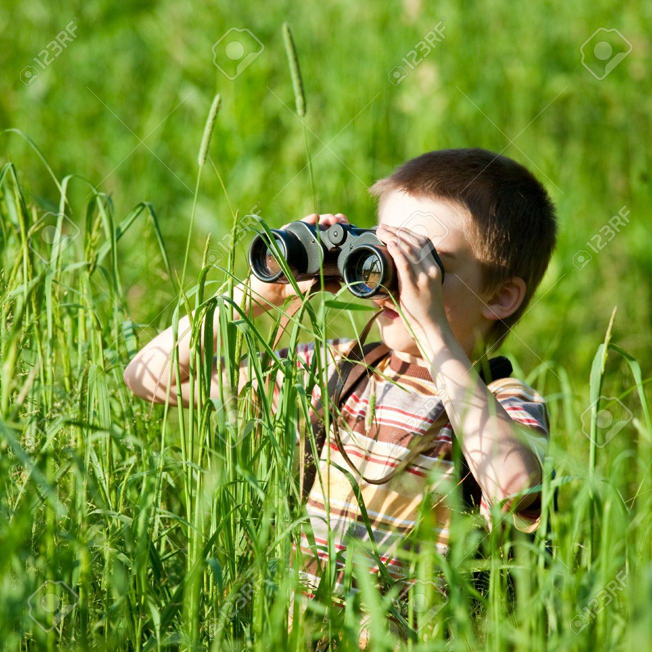Young boy in a field looking through binoculars Stock Photo - 5111490