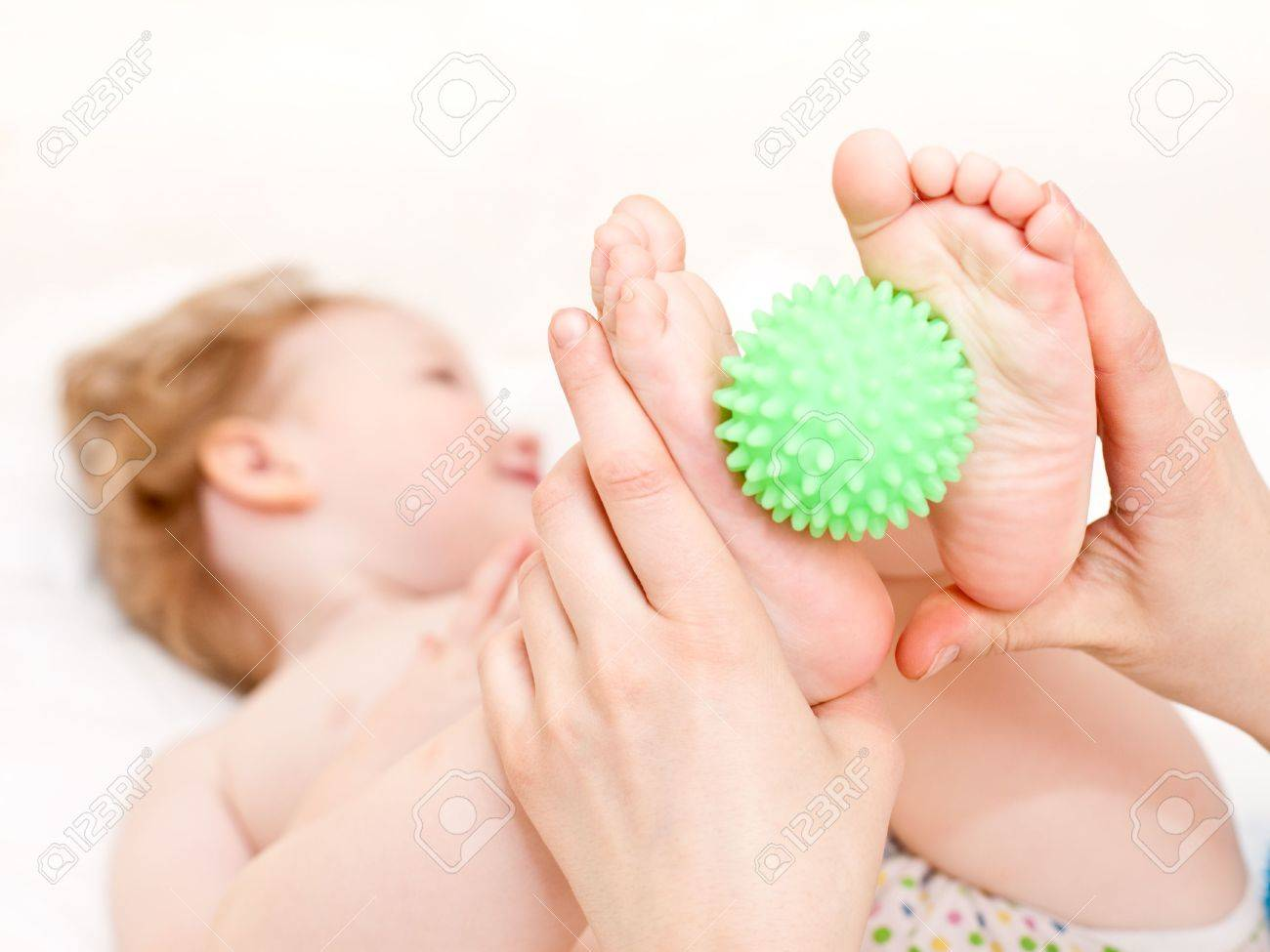 Masseur massaging child's feet with rubber device, shallow focus Stock Photo - 6694616