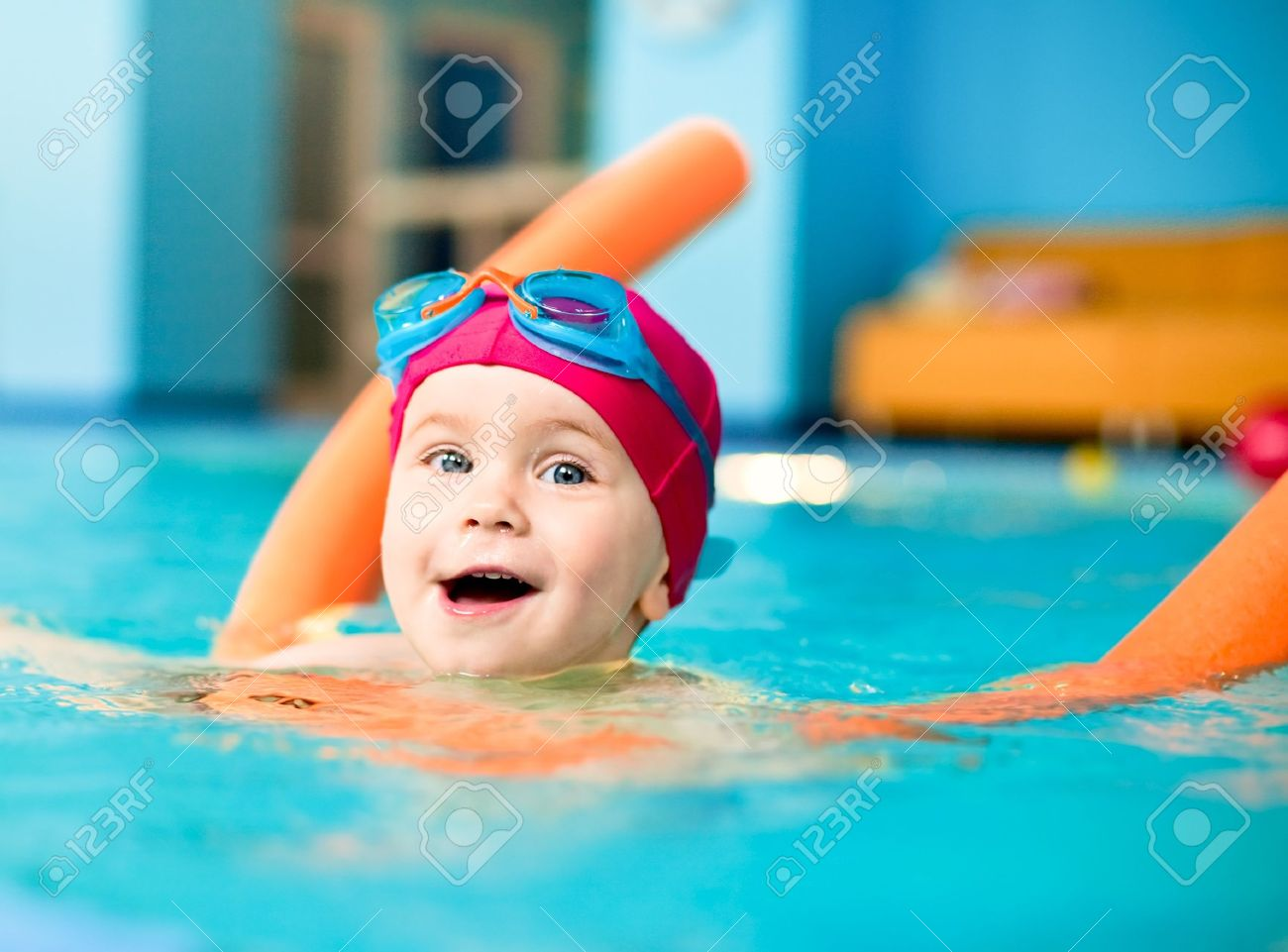 Happy little girl learning to swim with pool noodle - 6927304