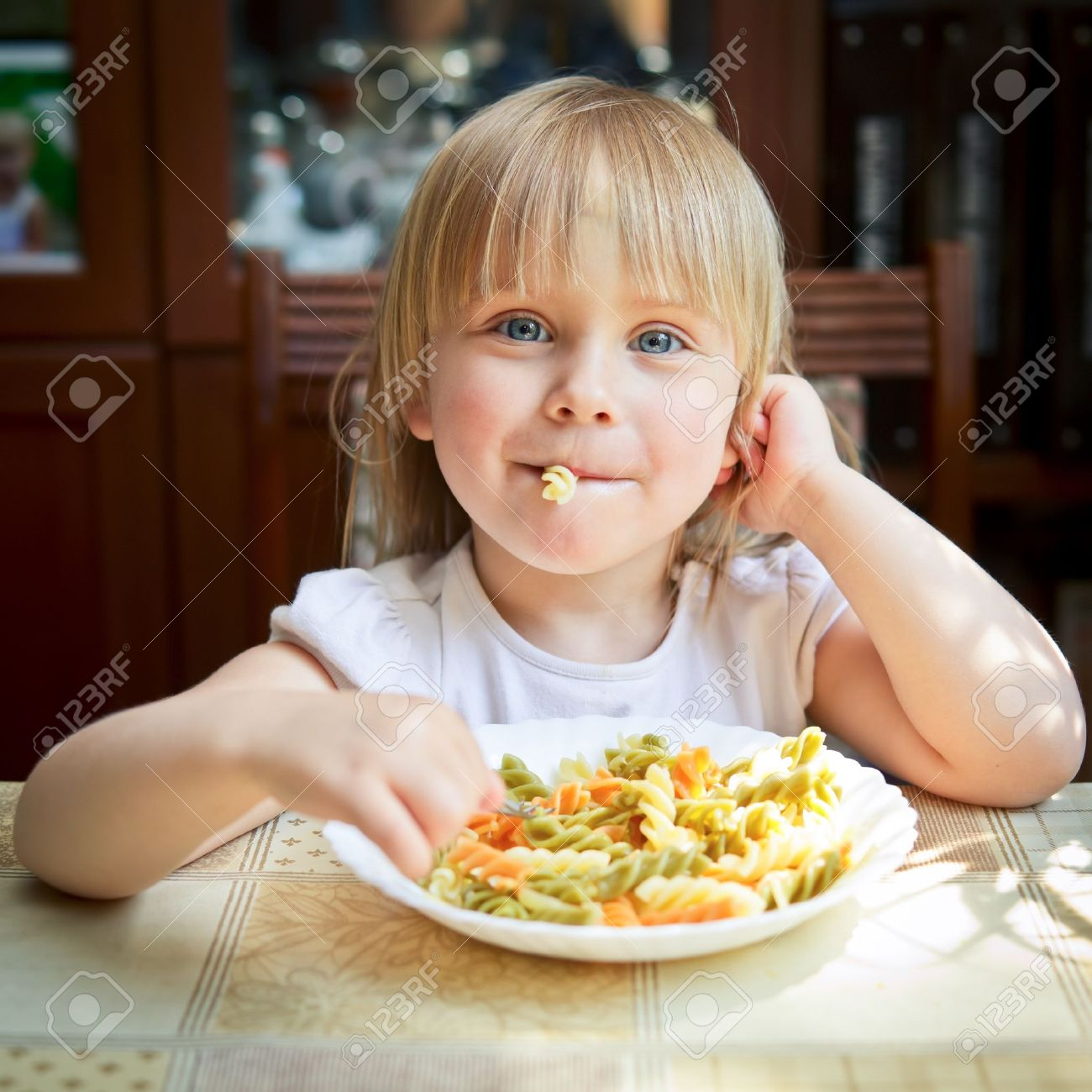 Cute little girl eating Fusilli Stock Photo - 13772570