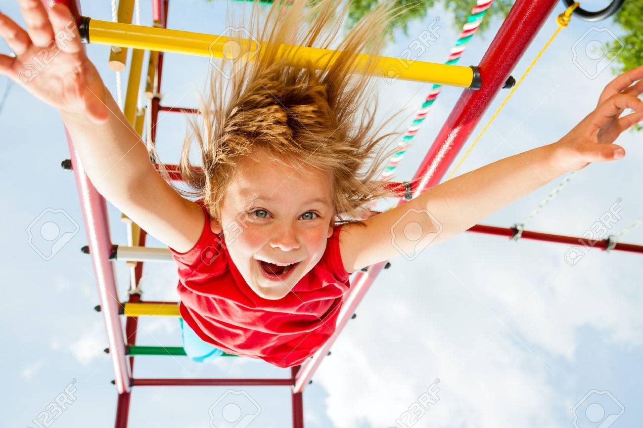 Little girl having fun playing on monkey bars - 29227770