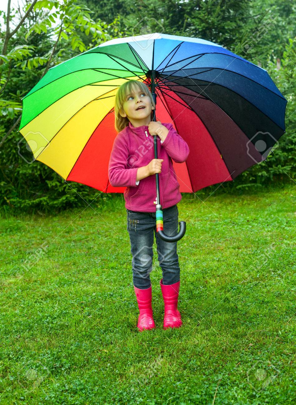 Little Girl Wearing Red Rubber Boots Hiding Behind Colorful Umbrella ...