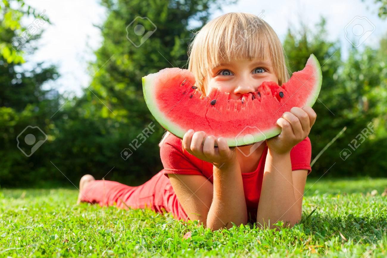 Happy little girl with watermelon in a garden - 36065425