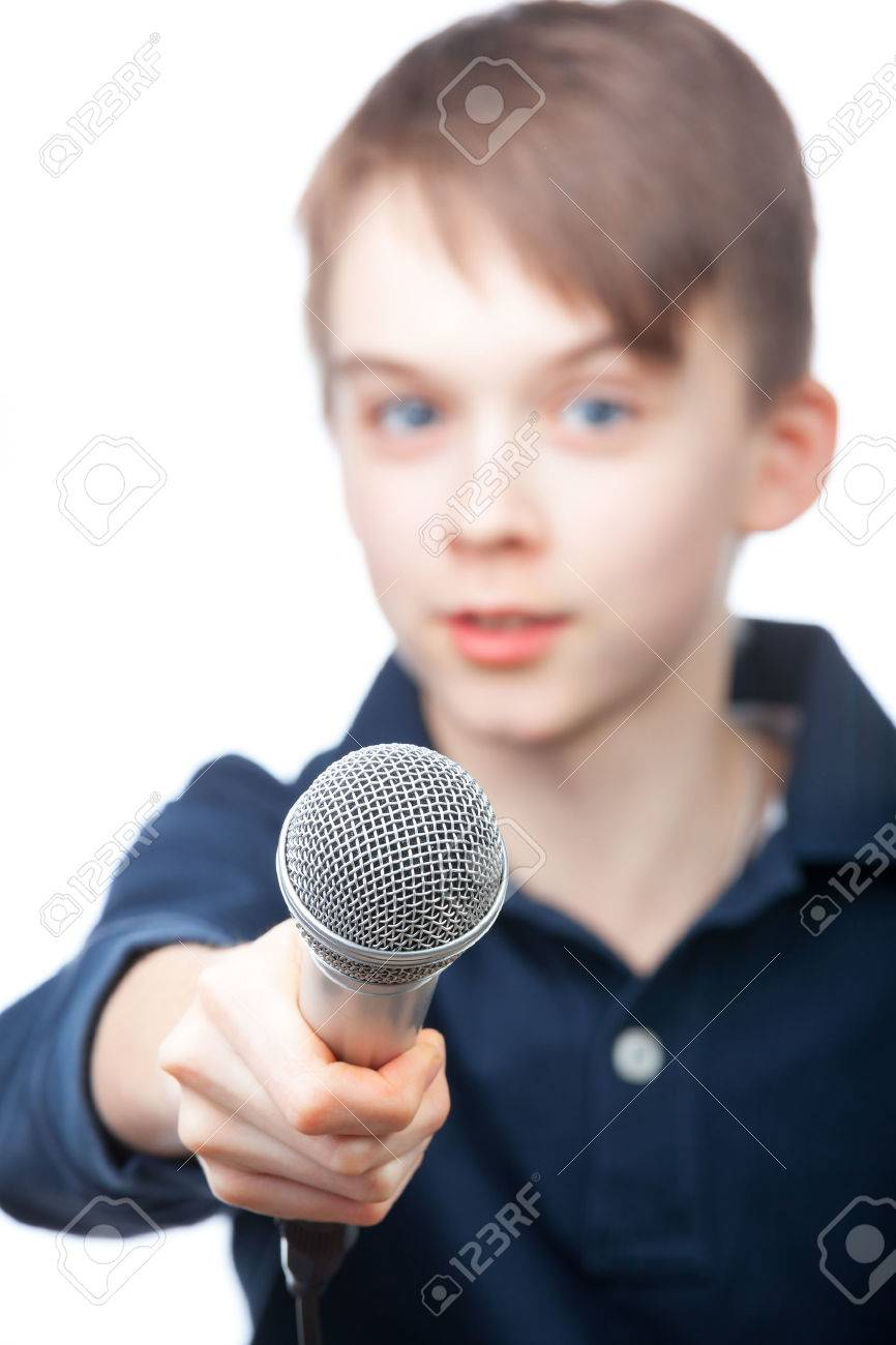 boy holding a microphone conducting an interview focus on boy holding a microphone conducting an interview focus on microphone face is blurred stock photo