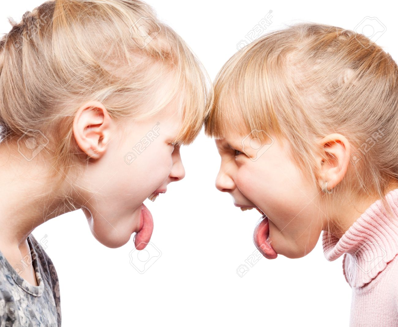 Two little girls unfriendly stick out tongues teasing each other - 49811230