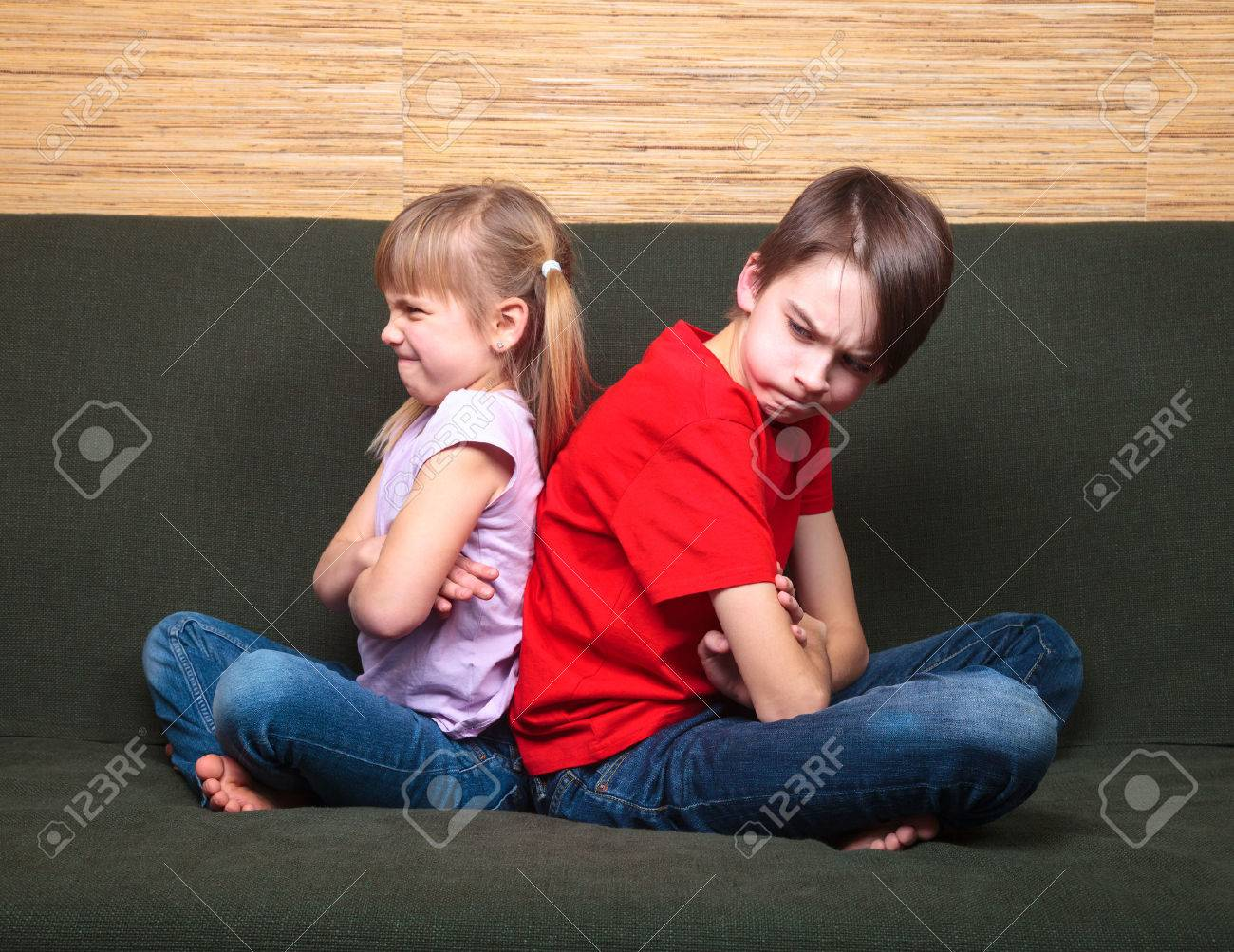 Brother and sister wearing casual clothes sitting on a green sofa at home arms crossed back to back angry with each other - 51199571