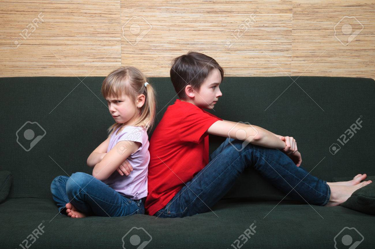 Brother and sister wearing casual clothes sitting on a green sofa back to back sad and frown - 51237240