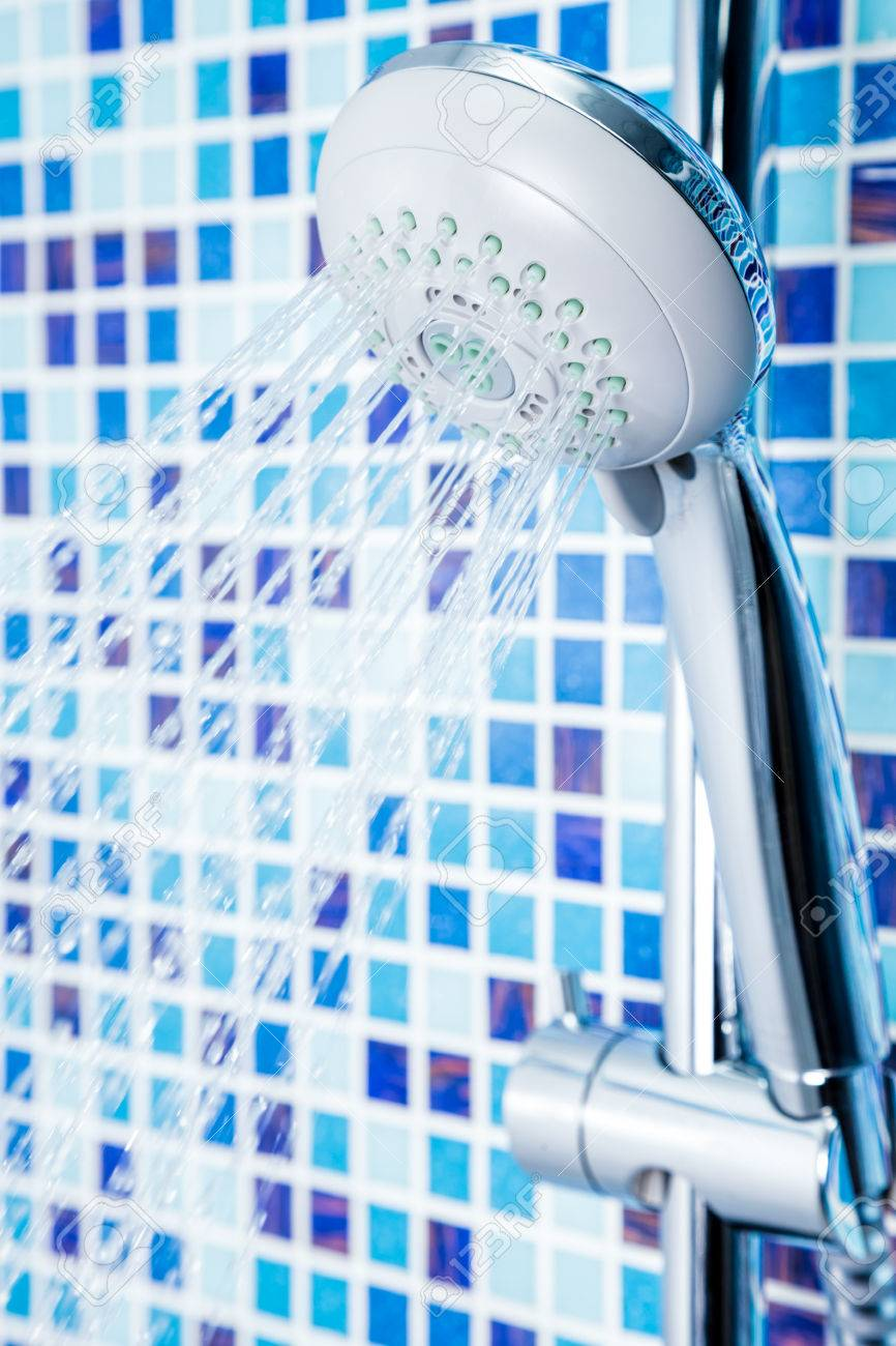 Shower Head With Running Water Against Blue Tiled Bathroom Wall ...