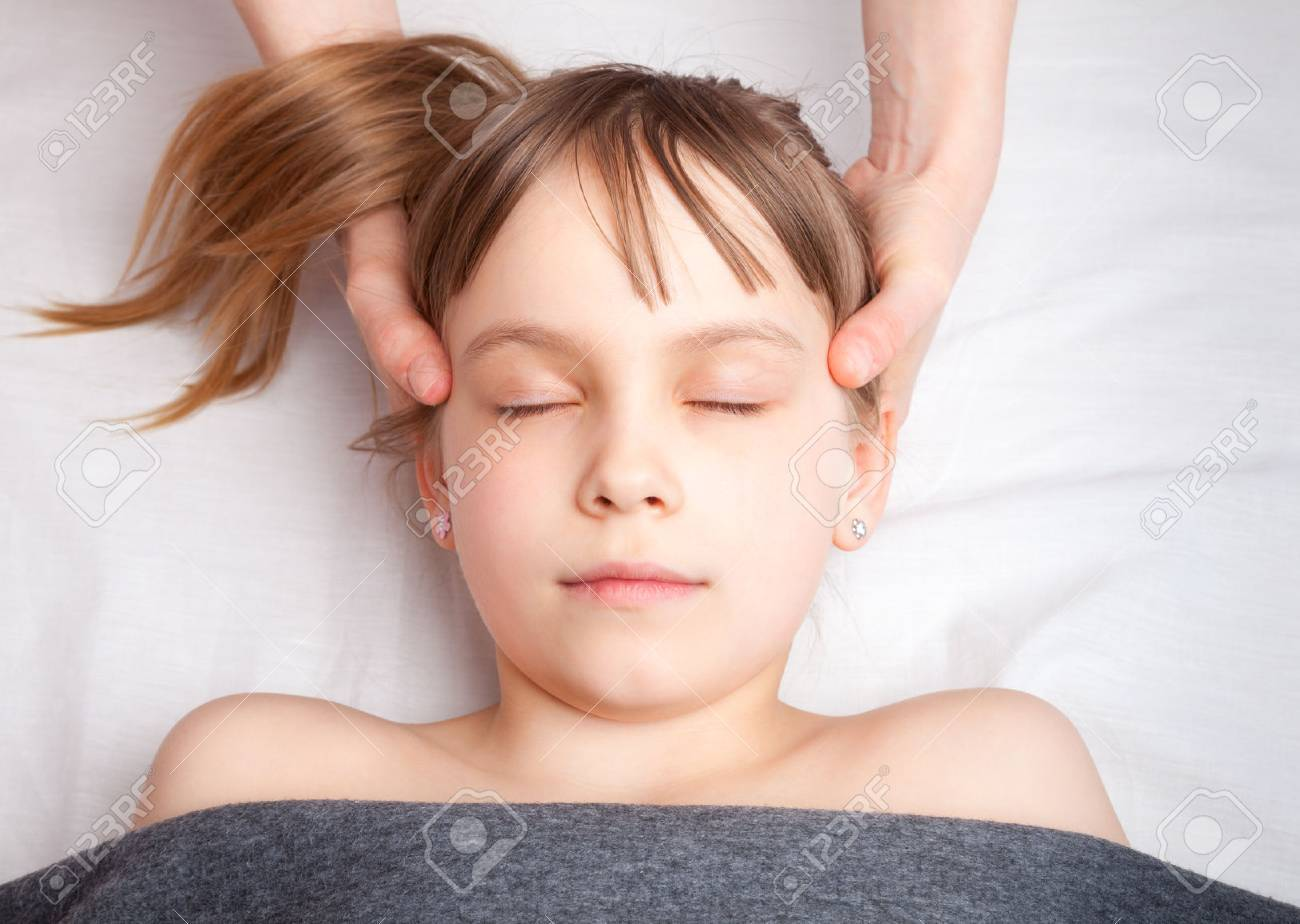 Elementary age girl's head being manipulated by an osteopath - an alternative medicine treatment - 78926226