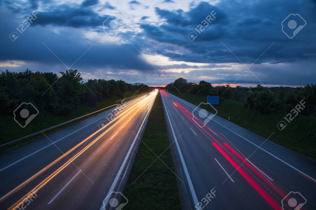 Dramatic evening sky over highway or motorway with car light trails at night, long exposure shot - 138276817