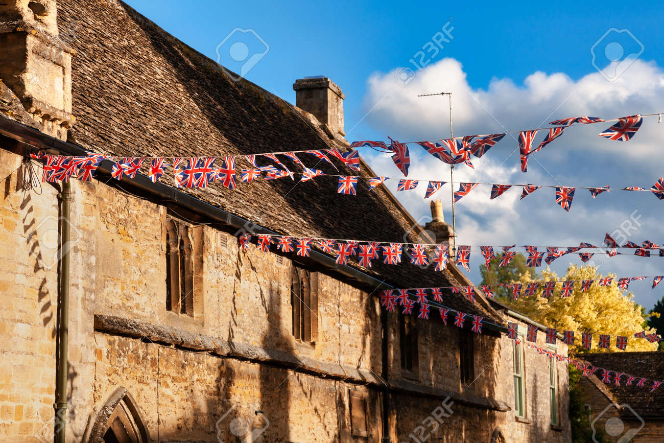Union Jack flag bunting hanging in a street, a festive decorations in Southwest England, UK - 164061904