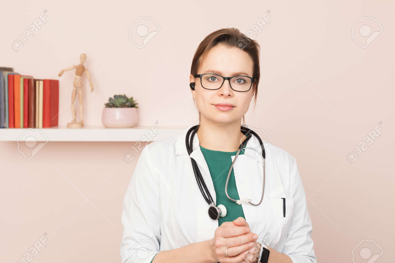 Portrait of confident young female doctor wearing white coat with stethoscope and earpiece standing in front of a camera at her home office performing online consultation - 164061906