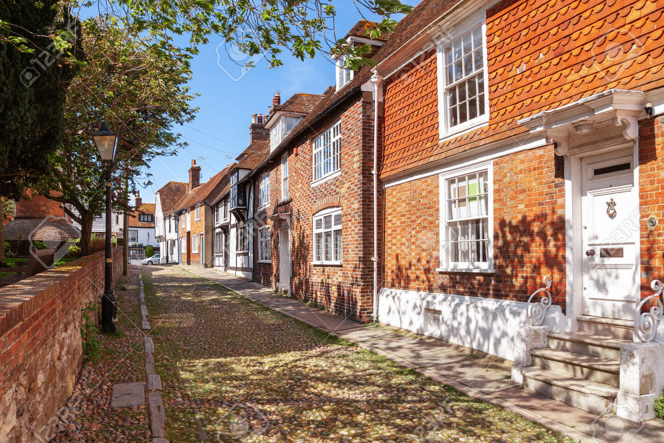 Old timber-framed and brick english houses along cobblestone street in picturesque Rye town, a popular travel destination in East Sussex, England, UK - 163985631