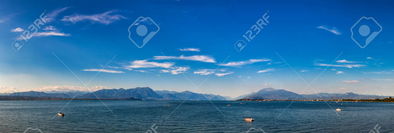 Panoramic view of Lake Garda (Lago di Garda or Benaco), the largest lake in Italy. Lake Garda is a popular holiday location on the edge of the Dolomites in Northern Italy - 165290945