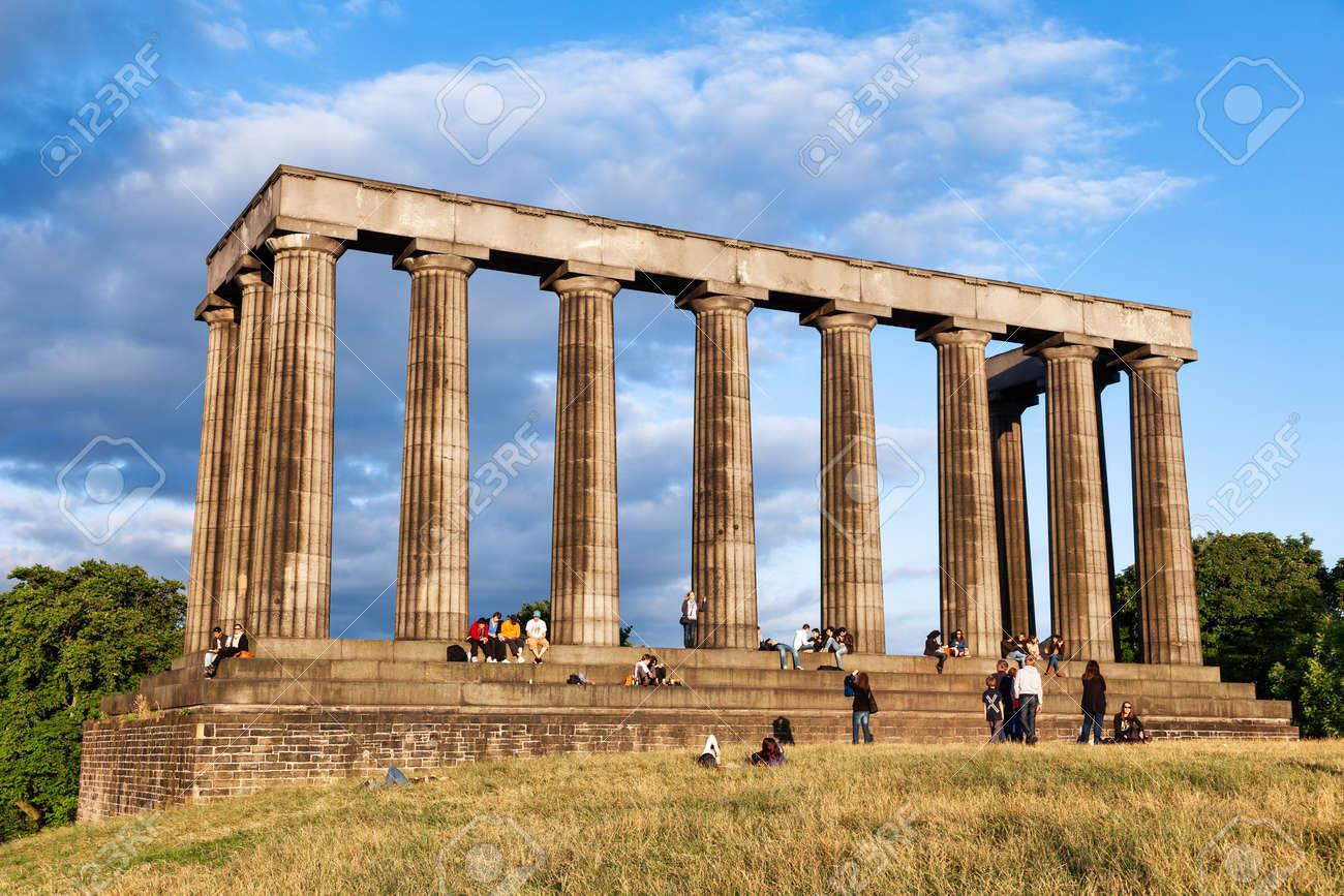 Edinburgh, UK - Aug 9, 2012: Tourists enjoy sunny evening at the National Monument of Scotland on the Calton Hill - 166775883