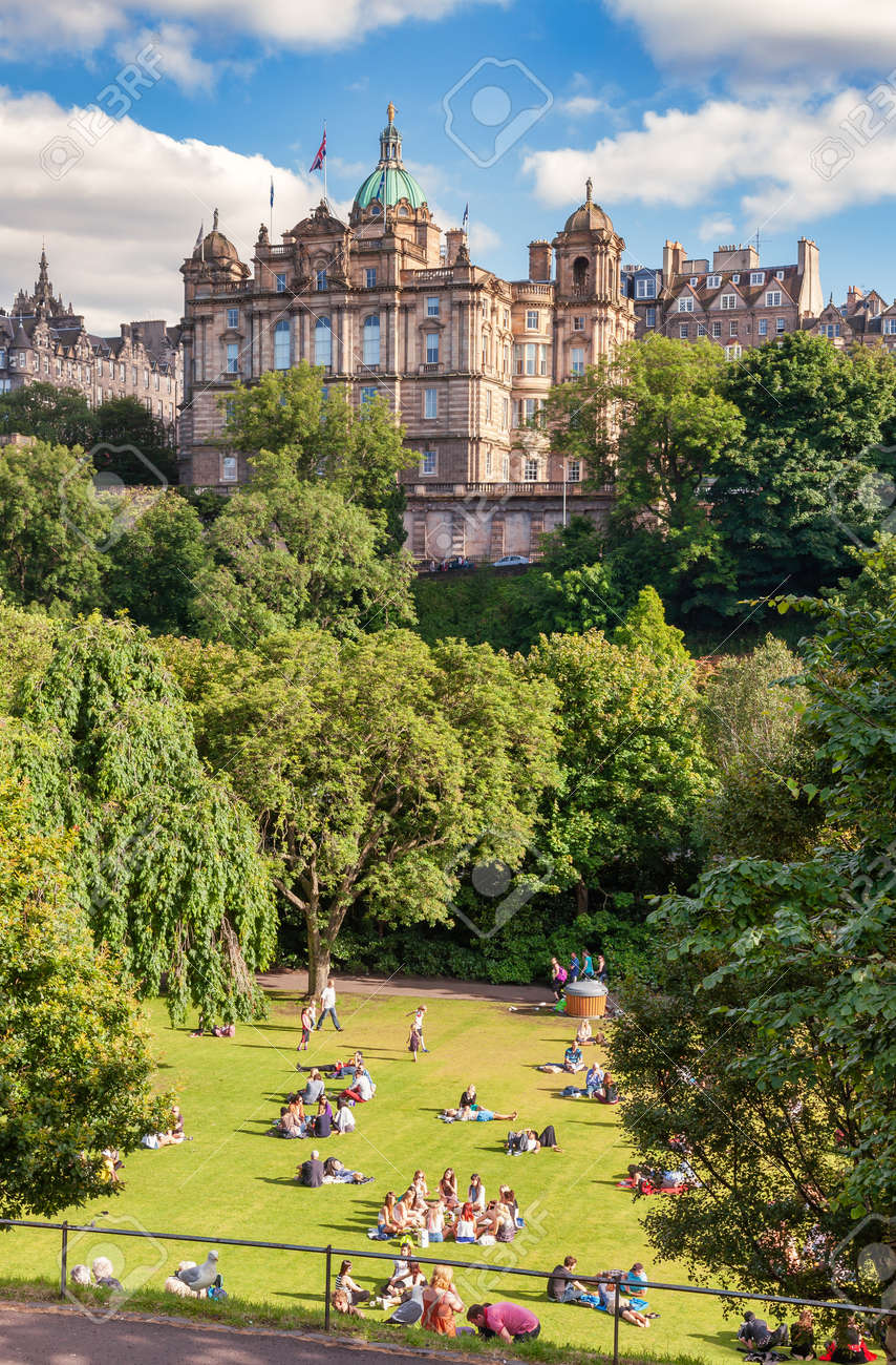 Edinburgh, UK - Aug 9, 2012: Locals and tourists enjoy warm sunny summer day relaxing and picnicking at the Princes Street Gardens, a famous public park in the city center - 166775886