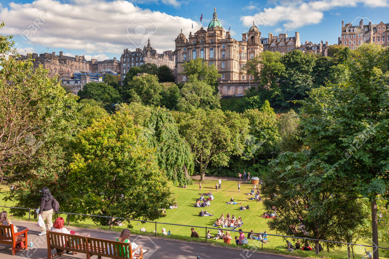 Edinburgh, UK - Aug 9, 2012: Locals and tourists enjoy warm sunny summer day relaxing and picnicking at the Princes Street Gardens, a famous public park in the city center - 166775891