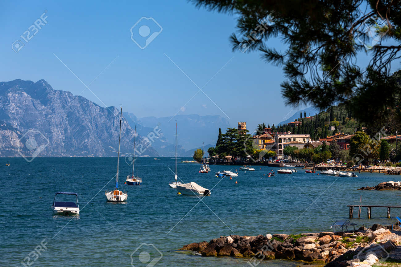 Pleasure boats moored near resort town on the eastern shore of Lake Garda in Northern Italy. Lake Garda is the largest lake in Italy and a popular holiday location on the edge of the Dolomites - 166389963