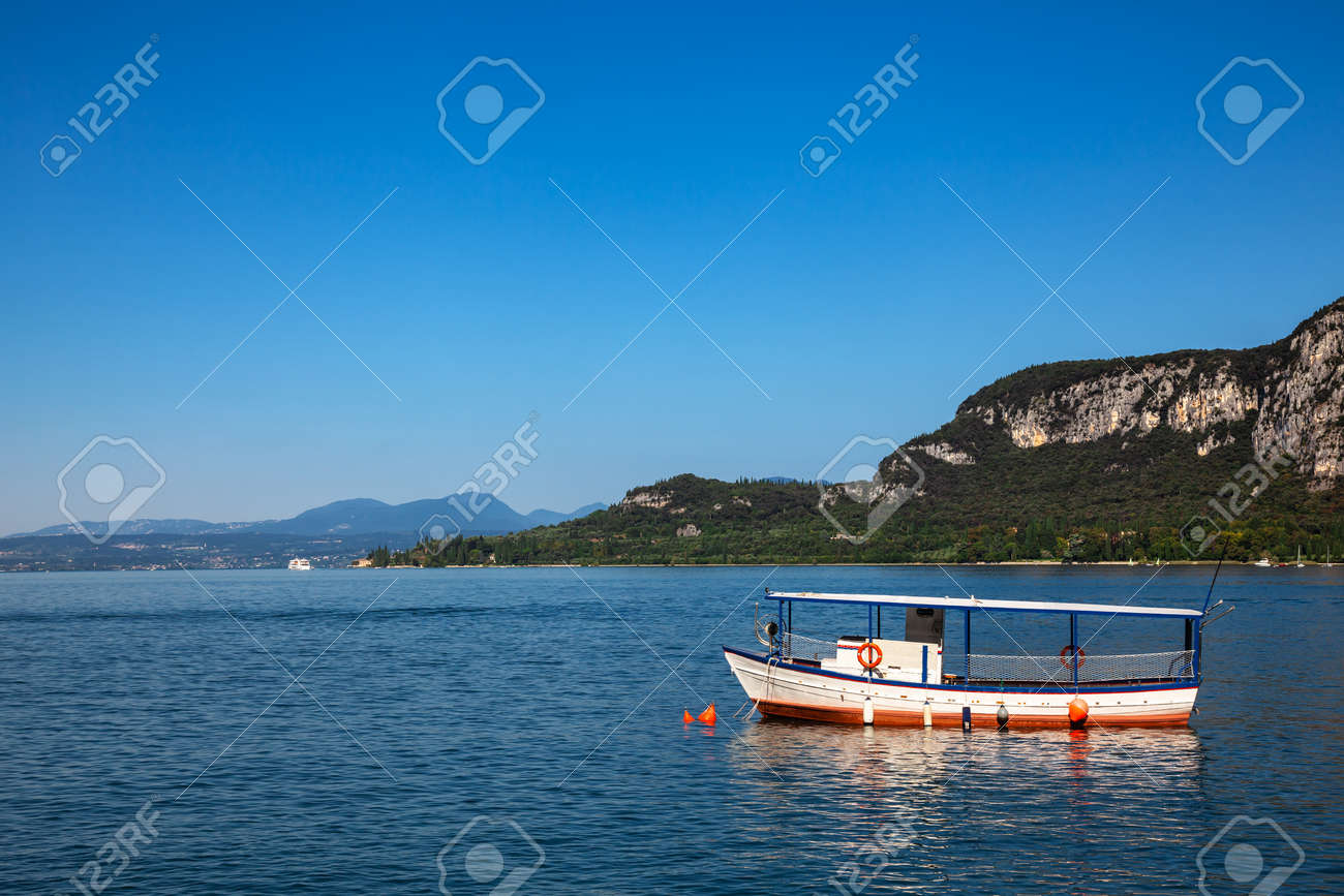 Pleasure boat moored near resort town on the eastern shore of Lake Garda in Northern Italy. Lake Garda is the largest lake in Italy and a popular holiday location on the edge of the Dolomites - 166390345