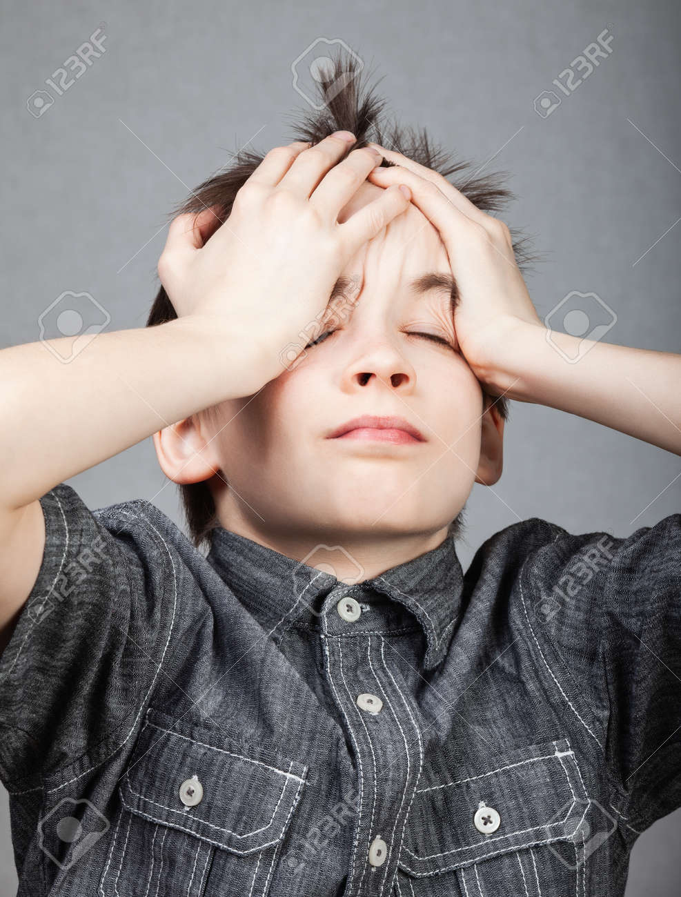 Portrait of schoolboy holding his head suffering from headache or stressed having learnind difficulties - 166814678